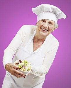 senior woman cook holding a bowl with salad against a pink backg