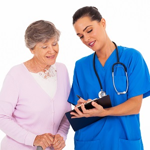 friendly young nurse helping senior woman with medical form